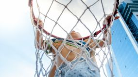 Closeup photo of active 3 years old toddler boy holding on basketball net ring. Concept of active and sporty children. Closeup image of active 3 years old stock photo