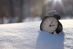 Closeup image of alarm clock in snow. Spring concept image Royalty Free Stock Image