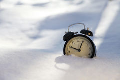 Closeup image of alarm clock in snow. Spring concept image Stock Images