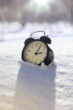 Closeup image of alarm clock in snow. Spring concept image Royalty Free Stock Images