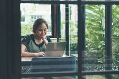 An asian business woman working and using laptop on wooden table in office with green nature background. Closeup image of an asian business woman working and stock photo