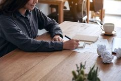 An asian businesswoman working and writing down on a white blank notebook with screwed up papers and laptop on table in office. Closeup image of an asian royalty free stock photo