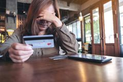 An Asian woman holding credit card with feeling stressed and broke stock image