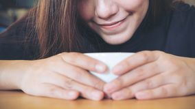 Closeup image of Asian woman holding , looking and smelling hot coffee on wooden table with feeling good Stock Photo
