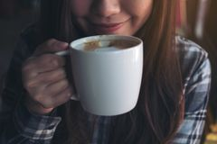 Closeup image of Asian woman smelling and drinking hot coffee with feeling good Royalty Free Stock Photo