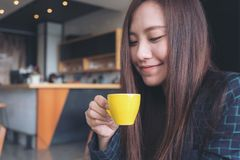 Closeup image of Asian woman smelling and drinking hot coffee with feeling good Stock Photography