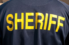 Closeup image of a back of a sheriff's deputy. With text sheriff in yelllow letters royalty free stock photo