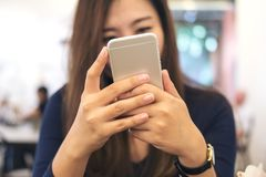 A beautiful Asian business woman holding , using and looking at smart phone in modern cafe stock photos
