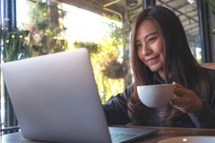Closeup image of a beautiful Asian business woman working and typing on laptop keyboard while drinking coffee Stock Photography