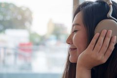 A beautiful Asian woman close her eyes and enjoy listening to music with headphone in modern cafe with feeling relax and happy. Closeup image of a beautiful Royalty Free Stock Images