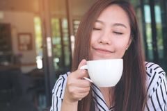 A beautiful Asian woman closing her eyes , smelling before drinking hot coffee with feeling good in cafe. Closeup image of a beautiful Asian woman closing her Royalty Free Stock Image