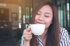 Beautiful Asian woman closing her eyes , smelling before drinking hot coffee with feeling good in cafe. Closeup image of a beautiful Asian woman closing her eyes Royalty Free Stock Image