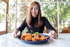 A beautiful asian woman enjoy eating fried chicken and french fries in restaurant. Closeup image of a beautiful asian woman enjoy eating fried chicken and french stock photos