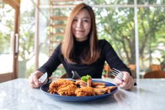A beautiful asian woman enjoy eating fried chicken and french fries in restaurant. Closeup image of a beautiful asian woman enjoy eating fried chicken and french royalty free stock photo