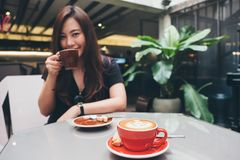 A beautiful Asian woman holding and drinking coffee with Americano coffee cup on glass table in loft cafe. Closeup image of a beautiful Asian woman holding and Royalty Free Stock Images