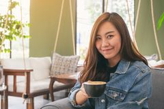 A beautiful asian woman holding and drinking hot coffee in cafe. Closeup image of a beautiful asian woman holding and drinking hot coffee in cafe royalty free stock photos