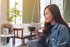 A beautiful asian woman holding and drinking hot coffee in cafe. Closeup image of a beautiful asian woman holding and drinking hot coffee in cafe stock photography