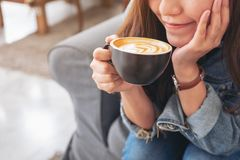 A beautiful asian woman holding and drinking hot coffee in cafe. Closeup image of a beautiful asian woman holding and drinking hot coffee in cafe royalty free stock image