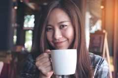 Closeup image of a beautiful Asian woman holding and drinking hot coffee with feeling good. In cafe Royalty Free Stock Photo
