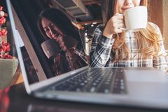 Closeup image of a beautiful Asian woman holding and drinking hot coffee reflection on laptop screen Royalty Free Stock Image