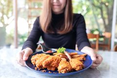 A beautiful asian woman holding and showing a plate of fried chicken and french fries in restaurant. Closeup image of a beautiful asian woman holding and showing royalty free stock photos