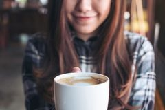 Closeup image of a beautiful Asian woman holding and showing a white mug while drinking hot coffee with feeling good. In cafe Stock Photos