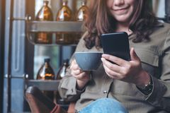 A beautiful asian woman holding , using and looking at smart phone while drinking coffee stock photo