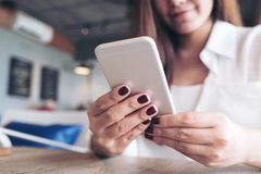 A beautiful Asian woman holding , using and looking at smart phone in modern cafe. Closeup image of a beautiful Asian woman holding , using and looking at smart royalty free stock images