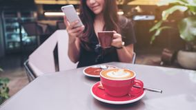 Closeup image of a beautiful Asian woman holding and using smartphone while drinking coffee with latte coffee cup on glass table. In loft cafe Stock Images