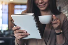 A beautiful Asian woman with smiley face holding and looking at a white blank notebook while drinking coffee in modern cafe. Closeup image of a beautiful Asian Royalty Free Stock Photography