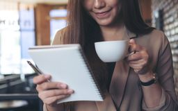 A beautiful Asian woman with smiley face holding and looking at a white blank notebook while drinking coffee. Closeup image of a beautiful Asian woman with Stock Photography