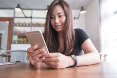 Closeup image of a beautiful Asian woman with smiley face holding and using smart phone Royalty Free Stock Image
