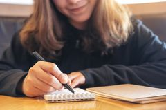 A woman writing on blank notebook on wooden table royalty free stock photos