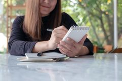 A beautiful business woman holding and writing on notebook in cafe with green nature background. Closeup image of a beautiful business woman holding and writing royalty free stock photography