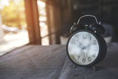 A black alarm clock on the table with blur background royalty free stock photography