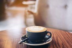Closeup image of a blue cup of hot latte coffee with latte art on vintage wooden table. In cafe royalty free stock photo