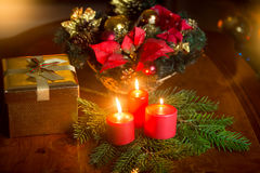 Closeup image of burning Christmas candles on table next to gift Stock Photos