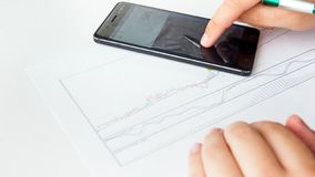 Closeup image of business analyst using smartphone calculator while analyzing stocks sales graph. Closeup photo of business analyst using smartphone calculator royalty free stock photography