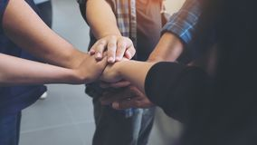 Business team standing and joining their hands together in office Royalty Free Stock Photo