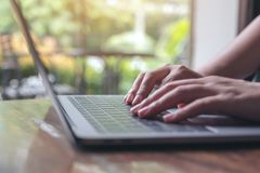 A business woman`s hands working and typing on laptop keyboard on wooden table with blur background. Closeup image of a business woman`s hands working and typing stock image