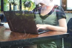 A business woman`s hands working and typing on laptop keyboard on wooden table with green nature background. Closeup image of a business woman`s hands working stock photography