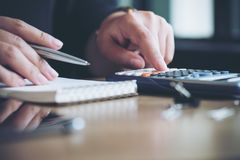 A business woman working , using calculator and writing on notebook in office Royalty Free Stock Photography