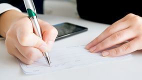 Closeup image of businesswoman putting signature on banking payment cheque. Closeup photo of businesswoman putting signature on banking payment cheque royalty free stock photography