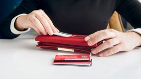 Closeup photo of businesswoman sorting credit cards and putting them in wallet. Closeup image of businesswoman sorting credit cards and putting them in wallet royalty free stock images