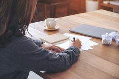 A businesswoman working and writing down on a white blank notebook with screwed up papers and laptop on table in office. Closeup image of a businesswoman working stock images