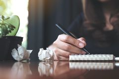 A businesswoman working and writing down on a white blank notebook with screwed up papers on table. Closeup image of a businesswoman working and writing down on Stock Image