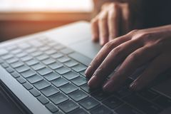 Closeup image of busineswoman working and typing on laptop keyboard on wooden table. Closeup image of business woman working and typing on laptop keyboard Stock Photos