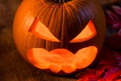 Scary jack-o-lantern with light inside close up. Closeup image of carved pumpkin with scary face and glowing from inside Halloween concept Stock Photography