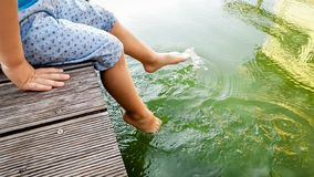 Closeup image of child sitting on the wooden pier at tiver and holding feet in water. Kids playing and splashing water. Closeup photo of child sitting on the stock photos