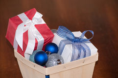 Closeup image of Christmas gifts in a small wooden basket Royalty Free Stock Photo